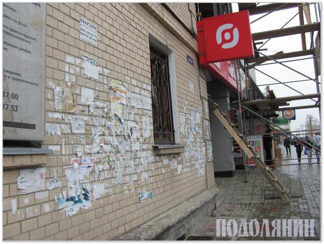 Через понаклеювані оголошення стіни будинків на Соборній - мов обшарпані